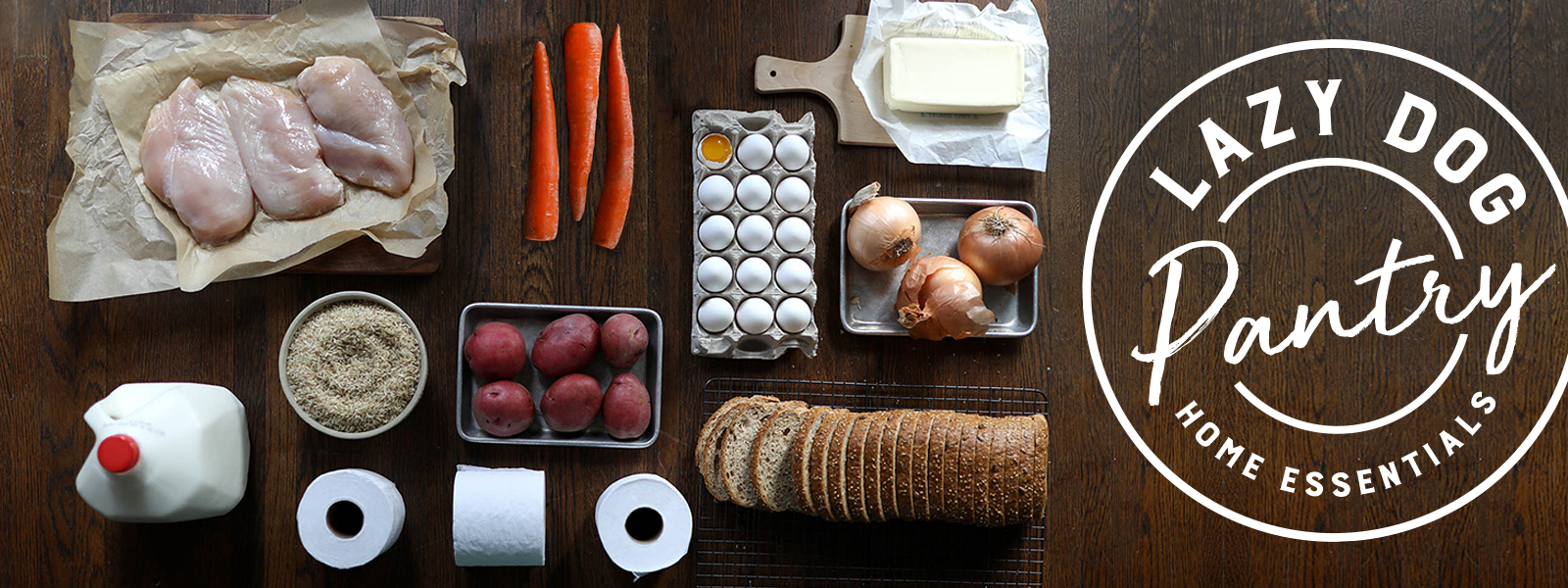 Lazy Dog Pantry Home Essentials:  Image of groceries: eggs, milk, toilet paper, chicken breast, carrots, butter, onions, potatoes, bread, rice