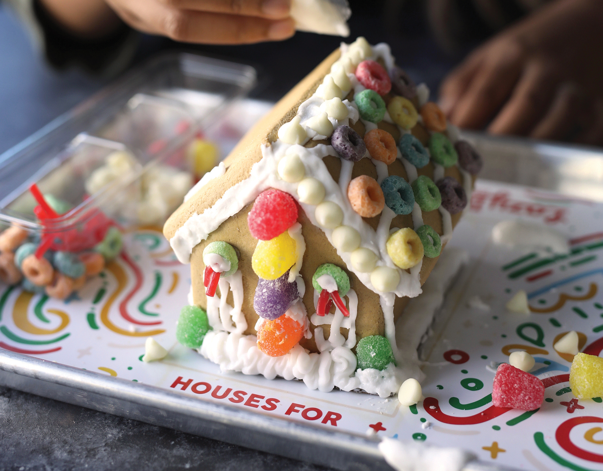 putting icing on a gingerbread house